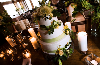 white-cake-with-green-fondant-ribbon-and-yellow-flowers-sits-on-tree-stump-surrounded-by-candles