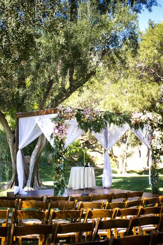 a-wooden-chuppah-featuring-foliage-with-light-colored-flowers-and-sheer-white-fabrics-hanging