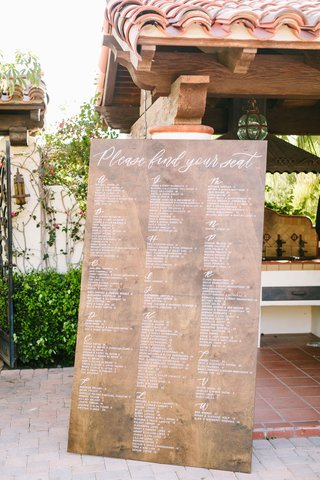 wedding-reception-spanish-style-venue-large-wood-sign-with-white-lettering-alphabetic-seating-chart