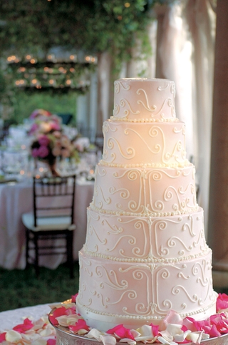 five-layer-cake-with-pale-pink-frosting-and-petals