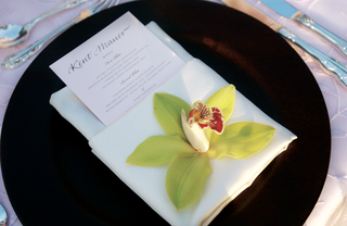 brown-charger-plate-with-white-napkin-and-flower