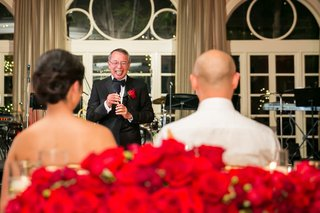 father-of-the-groom-laughs-while-giving-his-toast-to-the-newlyweds