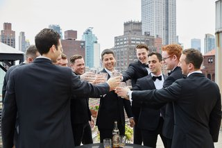 groom-and-groomsmen-on-rooftop-balcony-toasting-rocks-glasses-of-whiskey-scotch-tuxedos-new-york