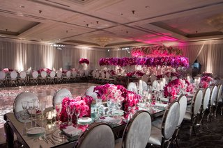 bright-pink-flower-centerpieces-on-mirror-table-with-velvet-grey-and-chrome-chairs-round-oval-backs
