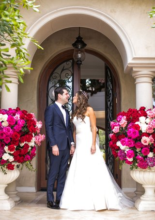 wedding-portrait-under-archway-at-beverly-hills-private-home-urns-filled-with-bright-pink-flowers