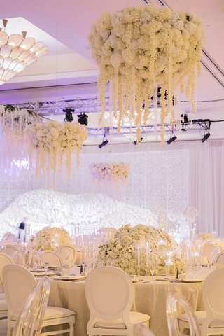 ivory-floral-fixtures-over-circular-tables-indian-hindu-wedding-ghost-chairs-candles-drapes