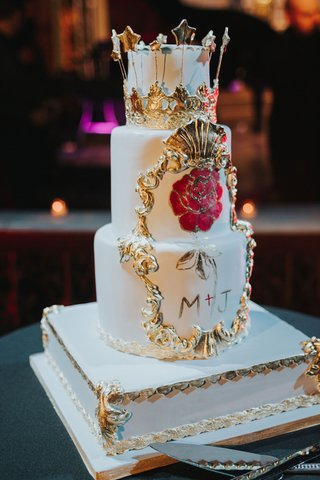 three-layer-wedding-cake-on-white-gold-stand-with-hand-painted-flowers-gold-details-crown