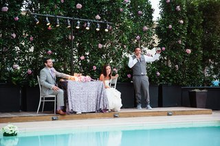 best-man-in-grey-vest-and-pants-white-shirt-gives-poolside-toast-to-newlyweds