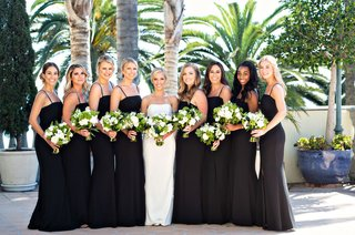 bride-in-strapless-wedding-dress-bridesmaids-in-black-bridesmaid-dresses-spaghetti-straps-greenery