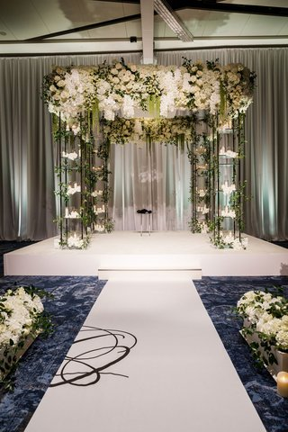 wedding-ceremony-ballroom-aisle-runner-white-stage-chuppah-candles-white-flowers-greenery-on-stage