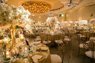 round-reception-tables-with-mirror-tops-gold-centerpiece-rose-orchid-flowers-chameleon-chairs