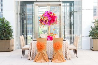 vibrant-fall-inspired-tablescape-orange-pink-purple-champagne-color-chair-covers-pom-poms