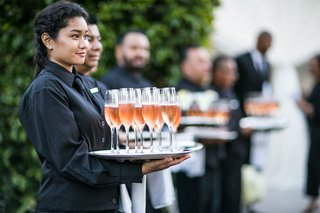 cocktail-hour-servers-ready-to-serve-champagne-and-rose-served-on-silver-tray-at-outdoor-wedding