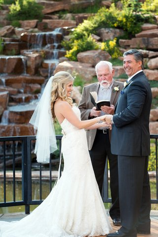 bride-smiles-at-groom-during-montana-wedding-ceremony-with-family-member-officiant