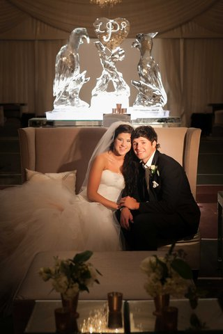 young-bride-in-monique-lhuillier-wedding-dress-with-groom-on-settee-in-front-of-parrot-ice-sculpture