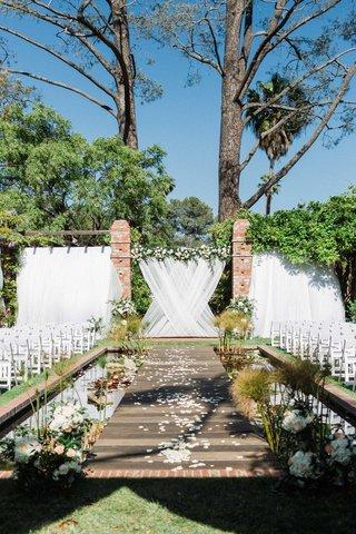 lily-pond-wedding-ceremony-venue-white-drapery-greenery-white-chairs-flowers-santa-barbara
