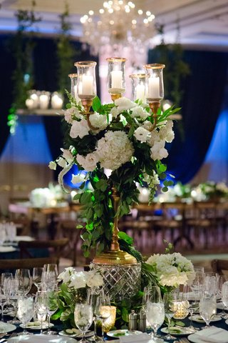 gold-candelabrum-wrapped-with-greenery-and-white-flowerson-crystal-stand