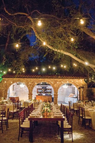 wedding-reception-long-wood-table-short-centerpiece-bistro-lights-hanging-from-trees-ranch-courtyard