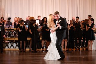 bride-in-a-strapless-pnina-tornai-dress-dances-with-groom-in-black-tuxedo