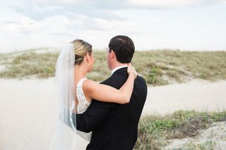 back-bride-in-alon-livne-lace-dress-and-groom-in-hugo-boss-suit-with-arms-around-each-other-beach