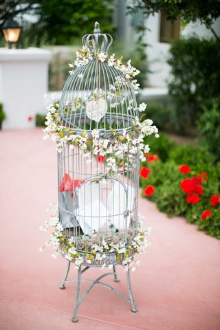 silver-and-white-bird-cage-as-wedding-reception-decor-adorned-with-small-white-flowers-and-notes