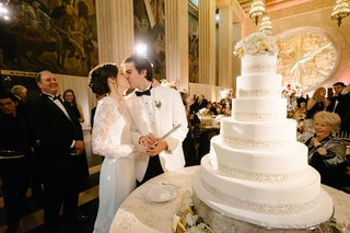 wedding-reception-cake-cutting-new-years-eve-bride-in-long-sleeve-illusion-lace-dress-kissing-groom