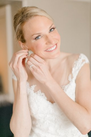 blonde-bride-putting-on-earrings-in-lace-wedding-dress-with-neutral-makeup