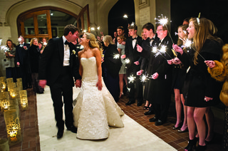 bride-and-groom-walk-up-aisle-as-guests-wave-sparklers