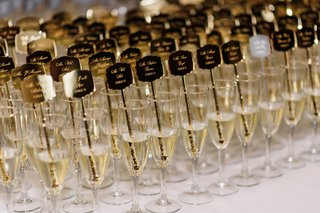 wedding-reception-ideas-escort-card-alternatives-drink-stirrer-gold-etched-champagne-flutes