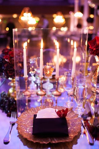guest-place-setting-with-gold-charger-on-mirror-table-with-red-centerpiece-and-taper-candlesticks