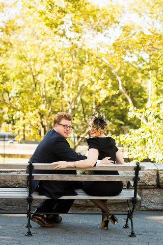 bride-in-a-black-off-the-shoulder-oscar-de-la-renta-dress-sits-with-groom-in-blue-suit-on-a-bench
