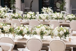 wedding-reception-long-wood-table-nailhead-trim-chairs-low-centerpiece-white-flowers-candles