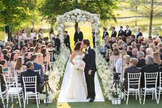 bride-and-groom-stop-and-share-kiss-after-walking-up-aisle-guests-watching-pink-and-white-flowers