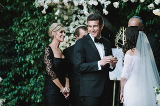 mother-of-groom-in-black-dress-stands-behind-groom-as-he-smiles-with-kiddush-cup-during-ceremony