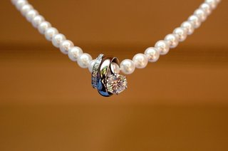 solitaire-engagement-ring-and-diamond-band-on-strand-of-pearls