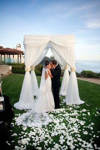 bride-and-groom-kiss-under-white-wedding-canopy