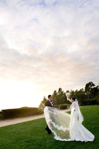 groom-and-bride-at-sunset-with-flower-trim-veil