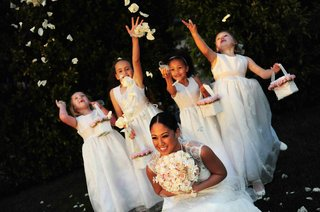 four-flower-girls-throw-white-rose-petals-on-top-of-bride