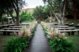 wooden-aisle-lined-with-ferns-pampas-grass-and-pink-flowers
