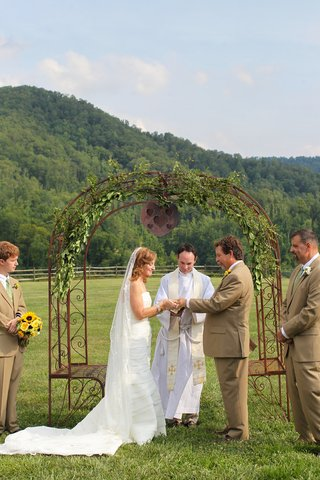 bride-and-groom-under-wrought-iron-arch-with-leaves