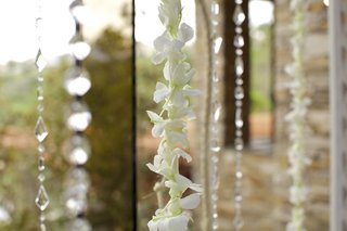 crystal-bead-strands-and-white-orchid-leis-against-window