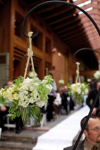 shepherd-hook-holding-white-flowers-hanging-from-rope
