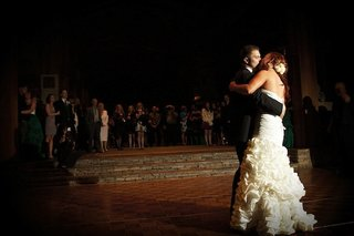 bride-and-groom-kiss-on-wood-dance-floor-at-reception