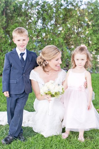 bride-in-a-lace-watters-dress-with-cap-sleeves-ring-bearer-in-blue-suit-flower-girl-in-pink-dress