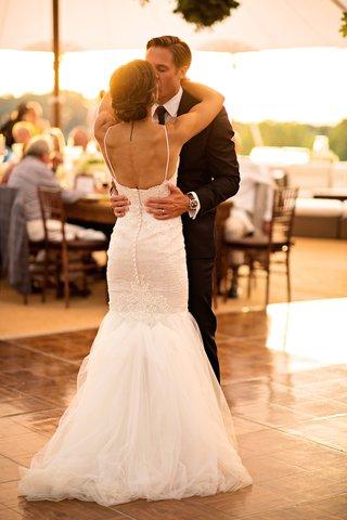 bride-in-berta-bridal-gown-kisses-groom-in-blue-ralph-lauren-tuxedo-during-first-dance