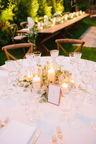outdoor-wedding-reception-pillar-candles-in-glass-stands-greenery-rose-gold-table-number-gold-rim