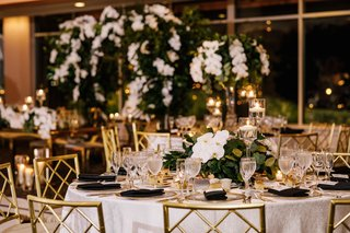 round-wedding-reception-table-black-napkin-gold-chairs-low-centerpiece-greenery-eucalyptus-orchid
