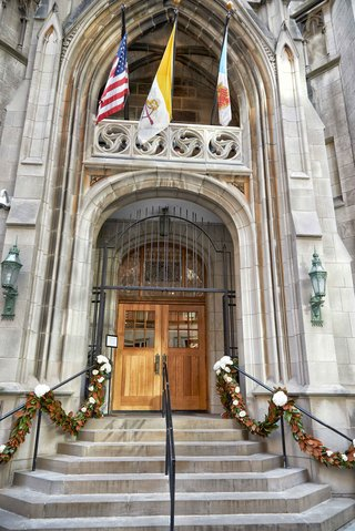 wedding-venue-in-chicago-st-james-chapel-with-magnolia-leaf-garlands-on-stair-hand-rail-flags