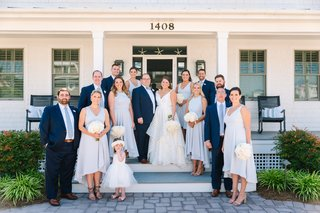 bride-in-striped-hayley-paige-wedding-dress-with-groom-in-navy-suit-bridal-party-on-porch