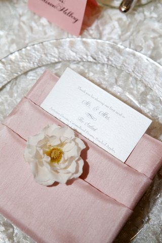clear-charger-plate-on-textured-linen-wedding-reception-single-flower-and-menu-tucked-in